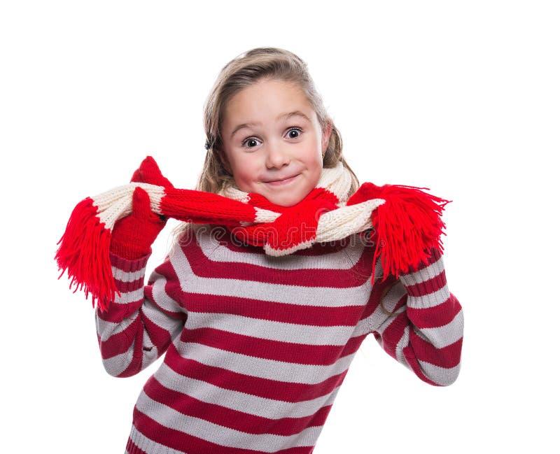 Menina alegre bonito que veste a camiseta, o lenço listrado e os mitenes feitos malha isolados no fundo branco Roupa do inverno imagens de stock