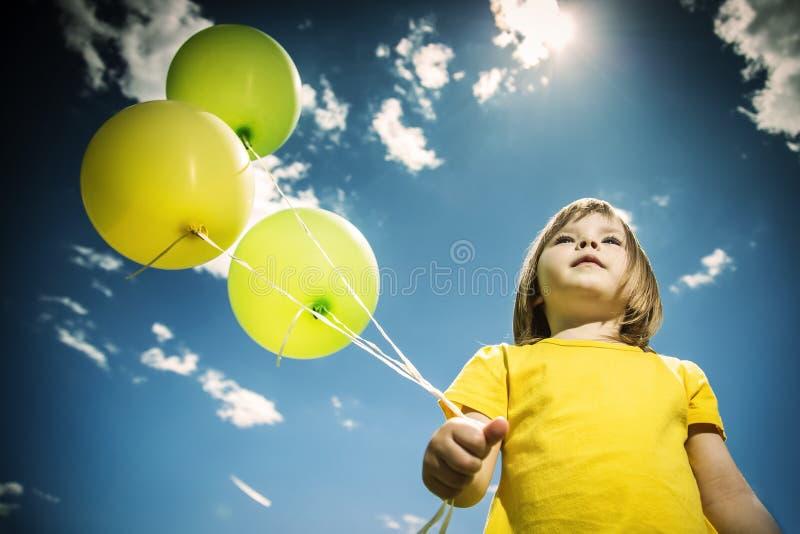 Menina alegre com balões coloridos Dia ensolarado do verão Ângulo de baixo de imagem de stock