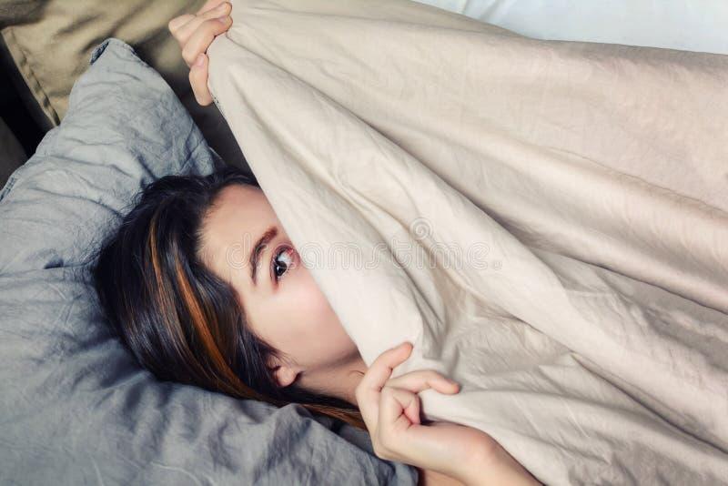A menina alegre com cabelo escuro, esconde sua cara sob uma cobertura Retrato de uma jovem mulher que se encontre em sua cama e n imagens de stock