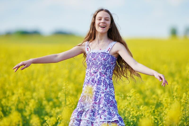 Menina alegre com a festão da flor no prado amarelo da colza fotos de stock royalty free