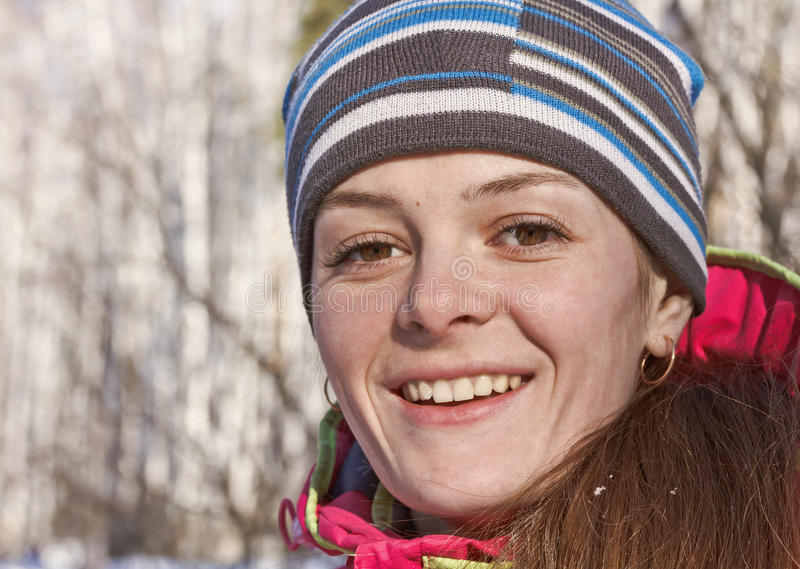 Menina alegre com os olhos marrons grandes em um fundo das árvores na floresta do inverno fotografia de stock
