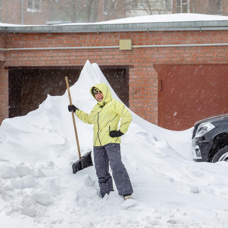 A menina alegre com a pá para a remoção de neve está perto de um monte de neve enorme perto da garagem fotos de stock royalty free
