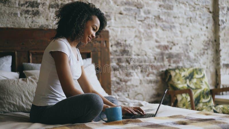 Menina alegre da raça misturada que datilografa no laptop para compartilhar dos meios sociais que sentam-se na cama em casa foto de stock royalty free
