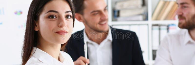 Menina alegre de sorriso bonita no olhar do local de trabalho imagem de stock