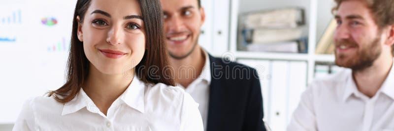 Menina alegre de sorriso bonita no olhar do local de trabalho fotografia de stock