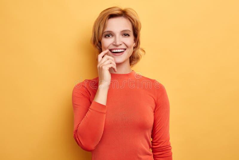 Menina alegre de sorriso bonita que toca em seus bordos imagem de stock royalty free
