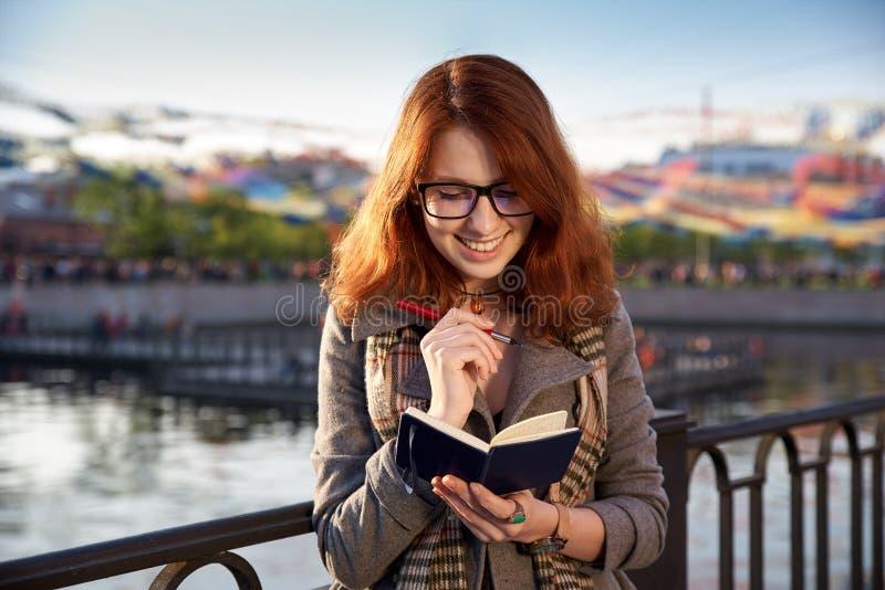 A menina alegre de sorriso faz uma anotação em um caderno, planeando como t foto de stock
