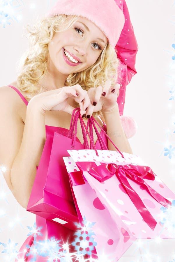 Menina alegre do ajudante de Santa com sacos de compra fotografia de stock
