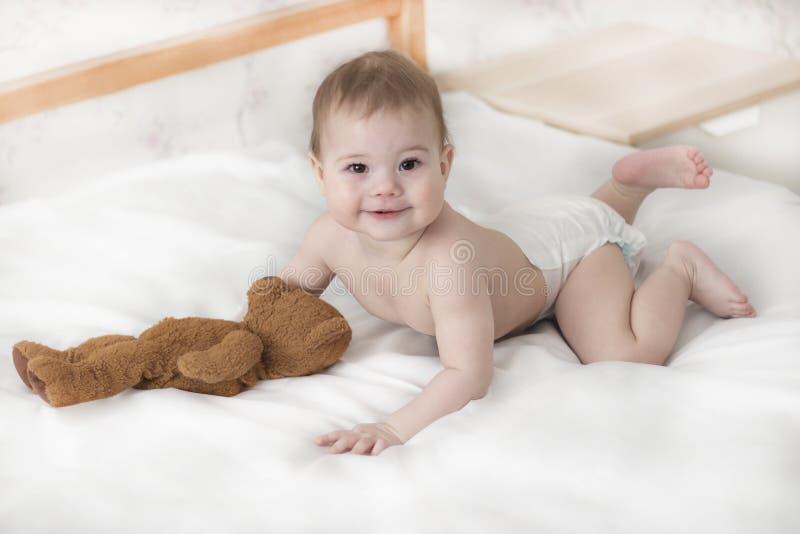 Menina alegre do bebê em um tecido que encontra-se com um urso de peluche Bebê bonito em um tecido que rasteja na cama, olhar na  fotografia de stock