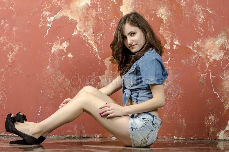 Menina alegre do jovem adolescente no short da sarja de Nimes imagem de stock