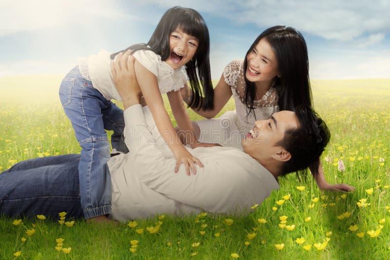 Menina alegre e seus pais que jogam no campo imagens de stock