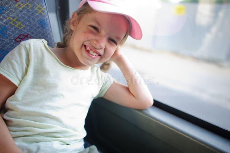 A menina alegre em um boné de beisebol cor-de-rosa vai pelo ônibus fotos de stock royalty free