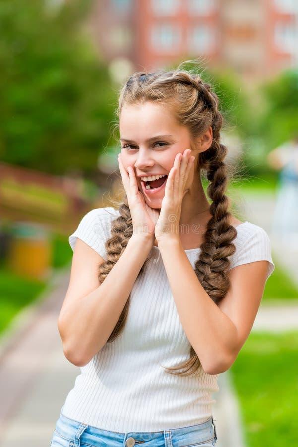 Menina alegre emocional com levantamento de duas tranças imagens de stock