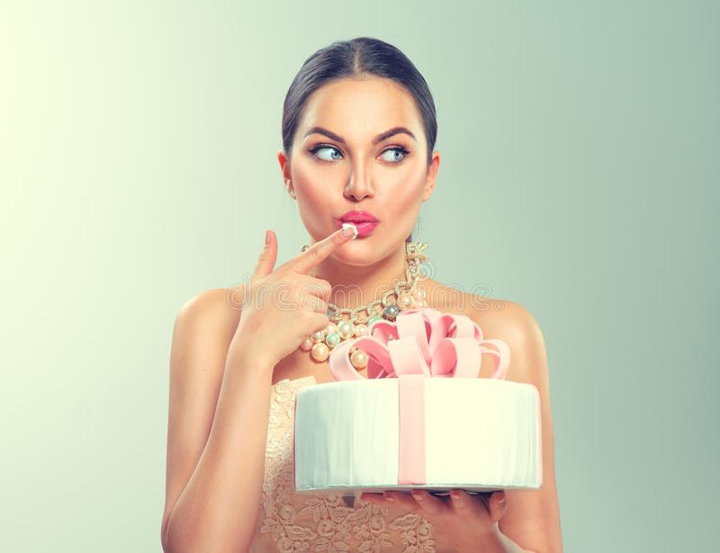 Menina alegre engraçada do modelo da beleza que guarda o bolo bonito grande do partido ou de aniversário imagens de stock