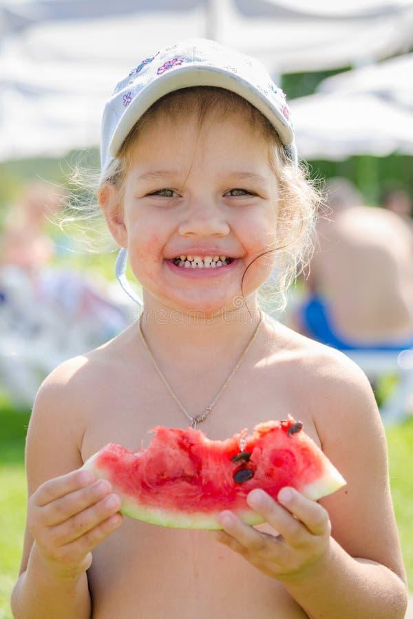 Menina alegre engraçada que come a melancia fotos de stock royalty free