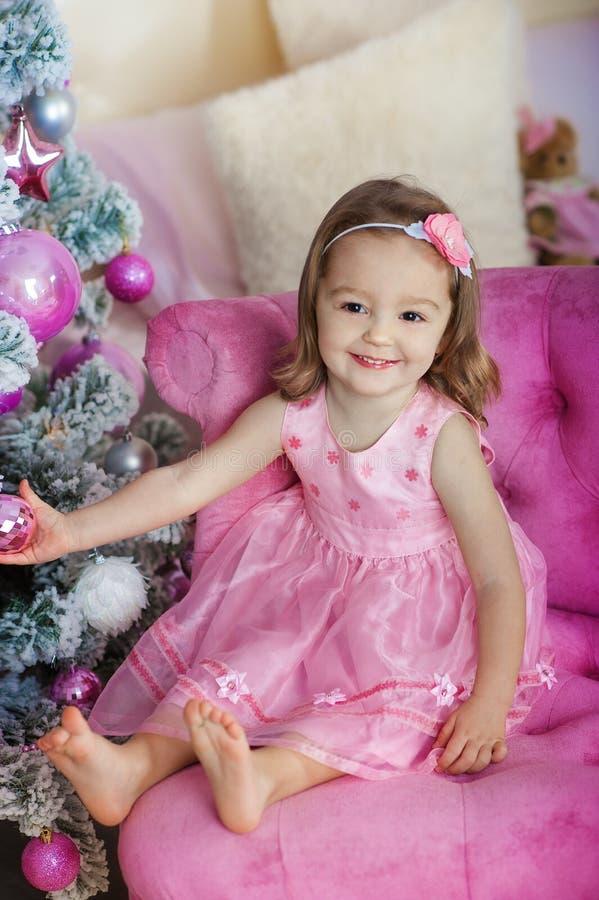Menina alegre feliz entusiasmado na Noite de Natal, sentando-se sob a árvore iluminada decorada Cartão ou tampa fotografia de stock royalty free