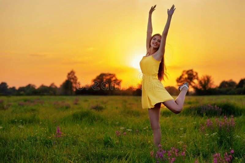 A menina alegre feliz está saltando na natureza sobre o por do sol do verão fotos de stock