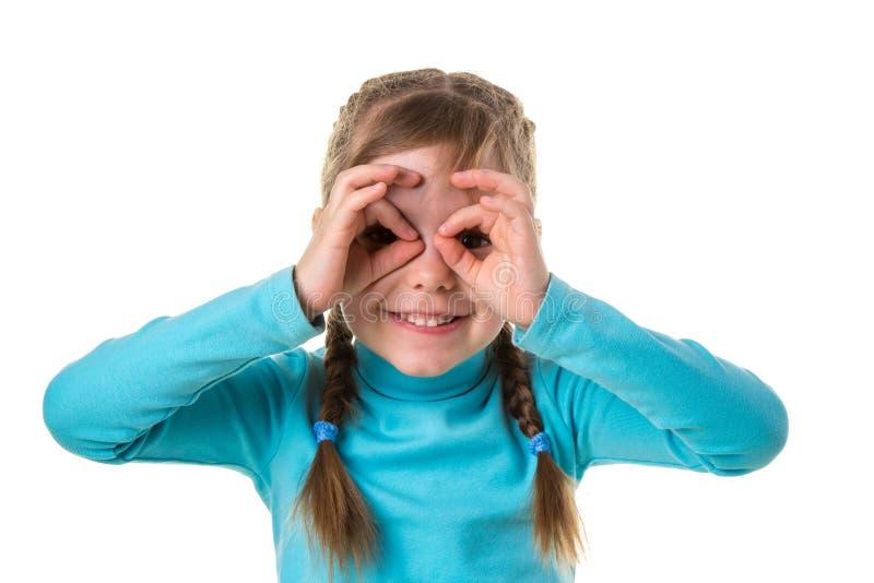 A menina alegre feliz mostra aprovações e vista através deles, fundo isolado branco da paisagem imagens de stock