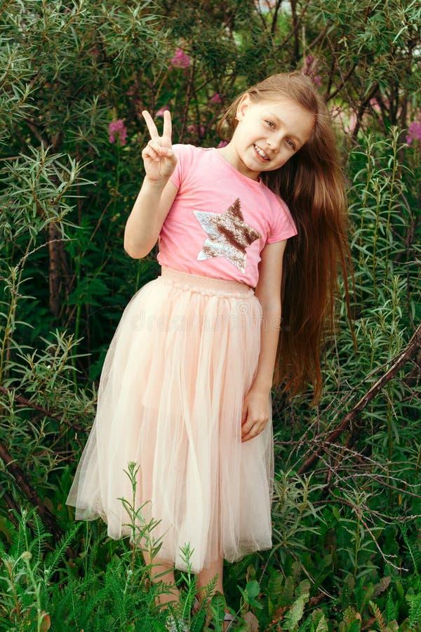 menina alegre feliz no parque do verão que mostra o gesto da paz fotos de stock royalty free