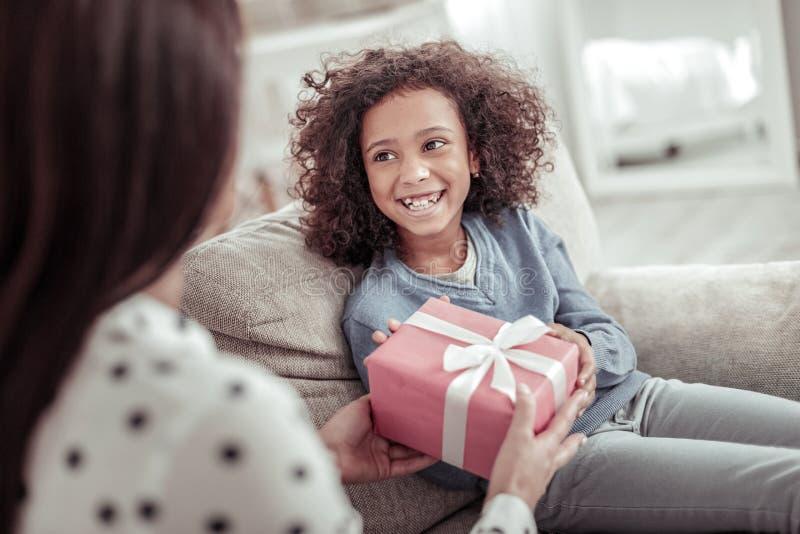 Menina alegre feliz que recebe um grande presente da mãe imagem de stock royalty free