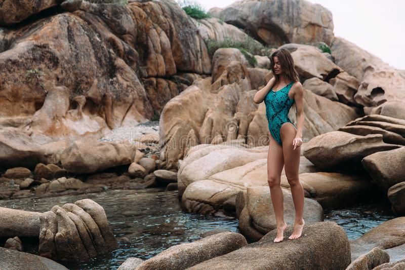 A menina alegre feliz veio primeiramente à praia rochosa selvagem, corridas em rochas, aprecia seu resto e o curso, veste um à mo imagens de stock
