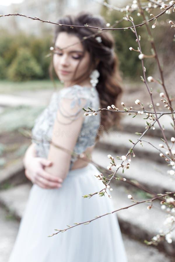 A menina alegre macia nova bonita com penteado bonito do casamento com um sorriso neve-branco no vestido leve está andando na mol fotos de stock royalty free
