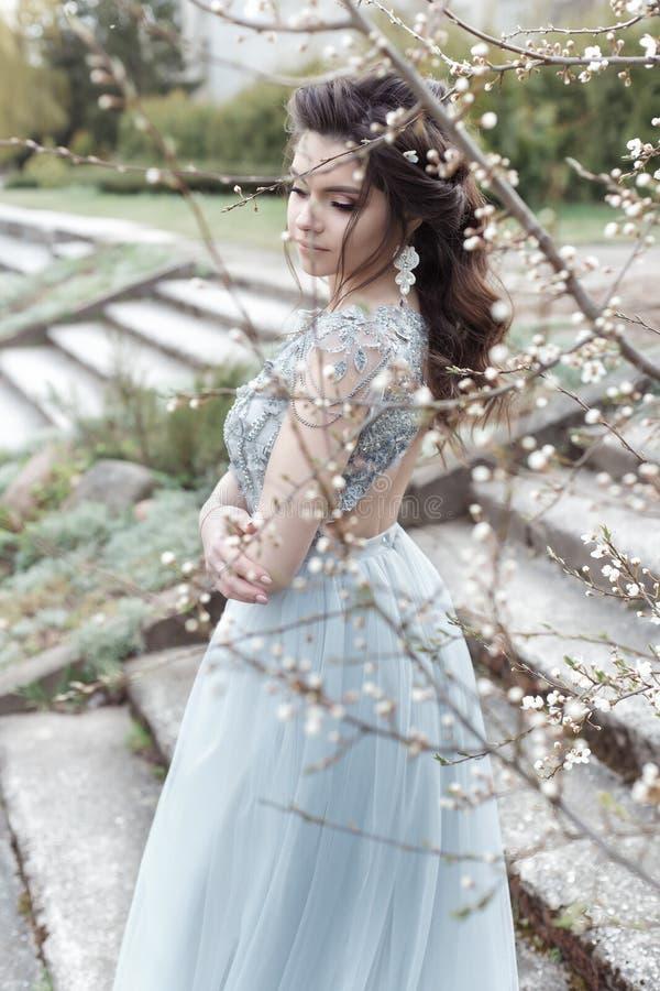 A menina alegre macia nova bonita com penteado bonito do casamento com um sorriso neve-branco no vestido leve está andando na mol foto de stock royalty free