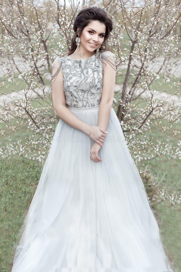 A menina alegre macia nova bonita com um penteado bonito do casamento com um sorriso neve-branco em um vestido leve está andando  fotografia de stock royalty free
