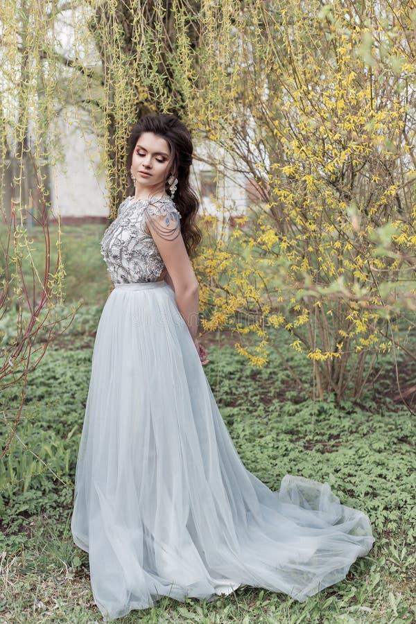 A menina alegre macia nova bonita com um penteado bonito do casamento com um sorriso neve-branco em um vestido leve está andando  fotos de stock royalty free