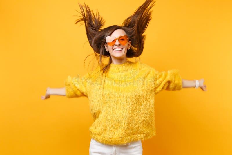 Menina alegre na camiseta da pele, vidros alaranjados do coração que enganam ao redor no salto do estúdio com o cabelo de fluxo i imagem de stock royalty free