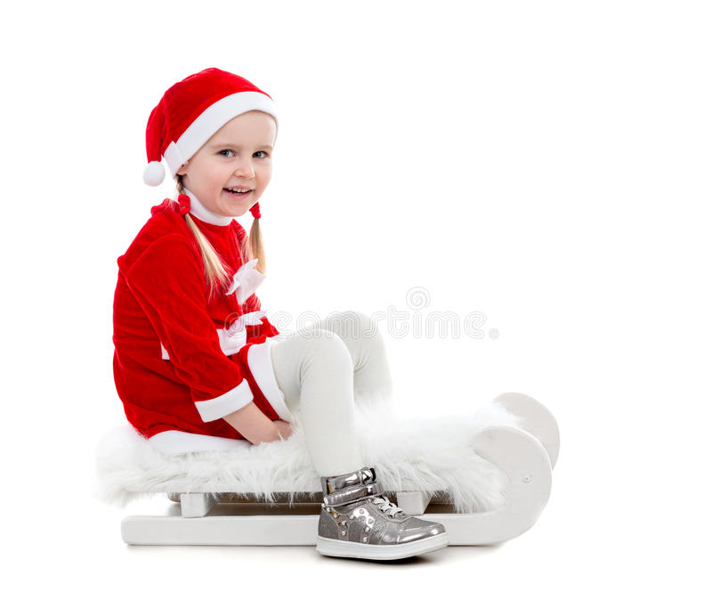 Menina alegre no terno de Santa que senta-se em um trenó imagens de stock royalty free