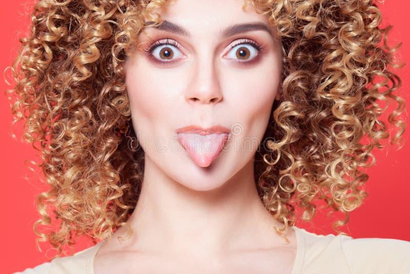 Menina alegre nova bonita com língua das mostras foto de stock royalty free