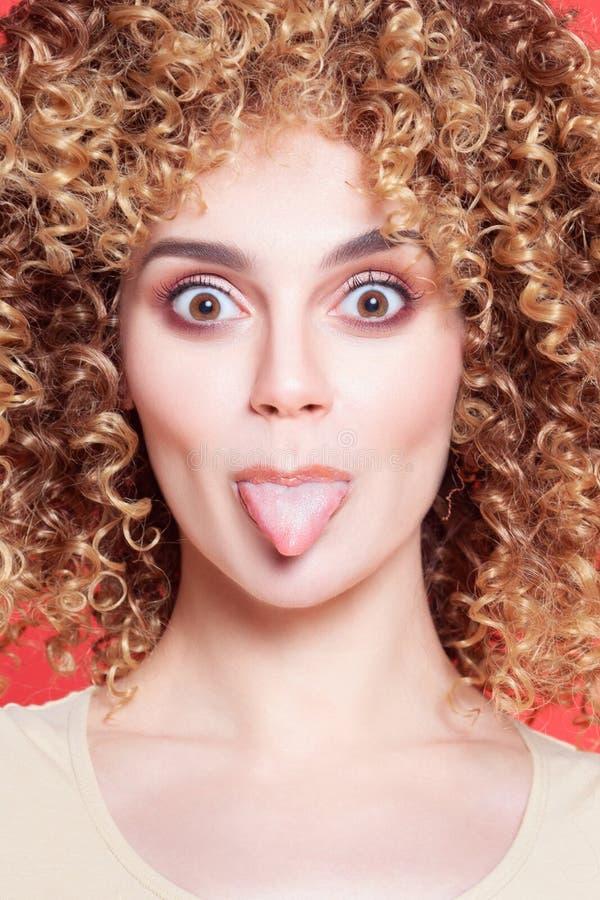 Menina alegre nova bonita com língua das mostras fotografia de stock