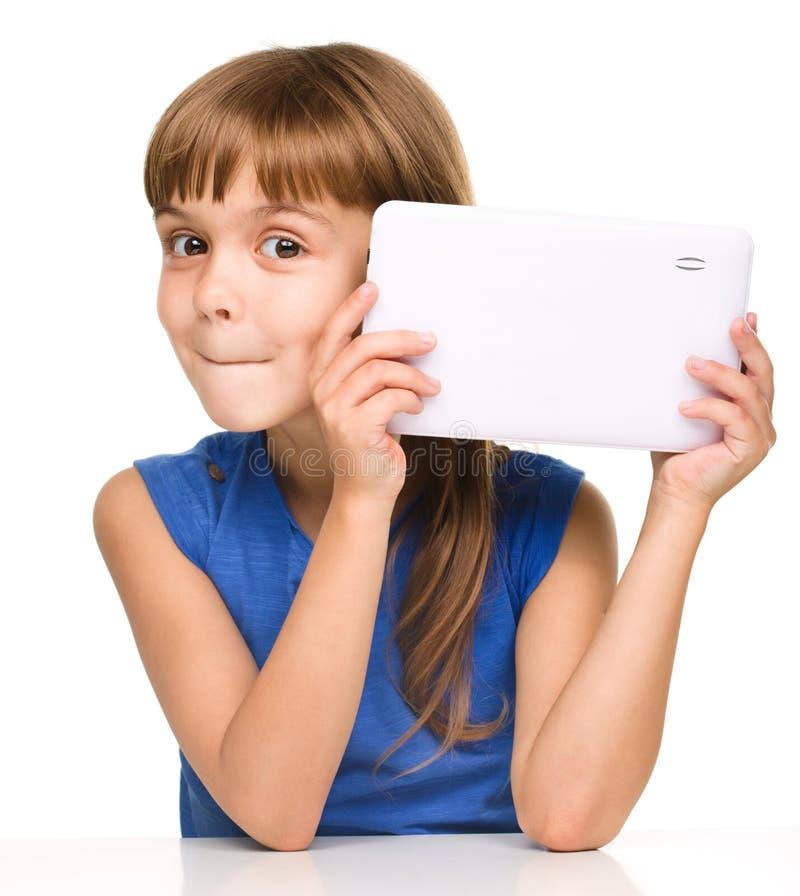 A menina alegre nova está usando a tabuleta foto de stock
