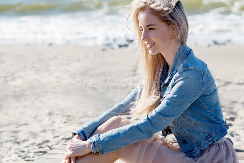 Menina alegre nova no litoral Mulher loura nova que senta-se na areia Saia bege na moda imagem de stock