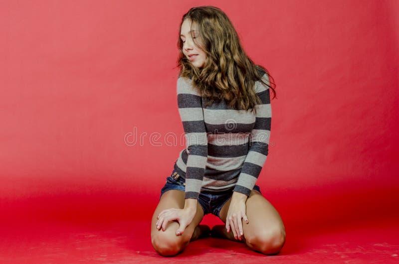 Menina alegre nova no short da sarja de Nimes e uma camiseta listrada que andam no estilo jovem fotos de stock royalty free