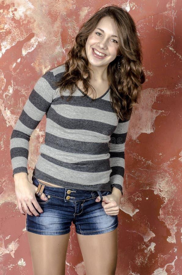 Menina alegre nova no short da sarja de Nimes e uma camiseta listrada que andam no estilo jovem foto de stock royalty free