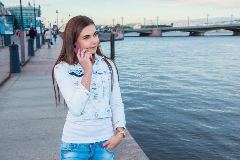 Menina alegre nova que chama com telefone de pilha ao apreciar g fotografia de stock royalty free