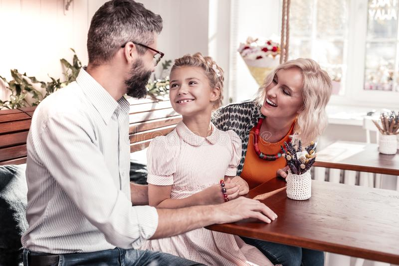 Menina alegre positiva que sorri a seu pai foto de stock