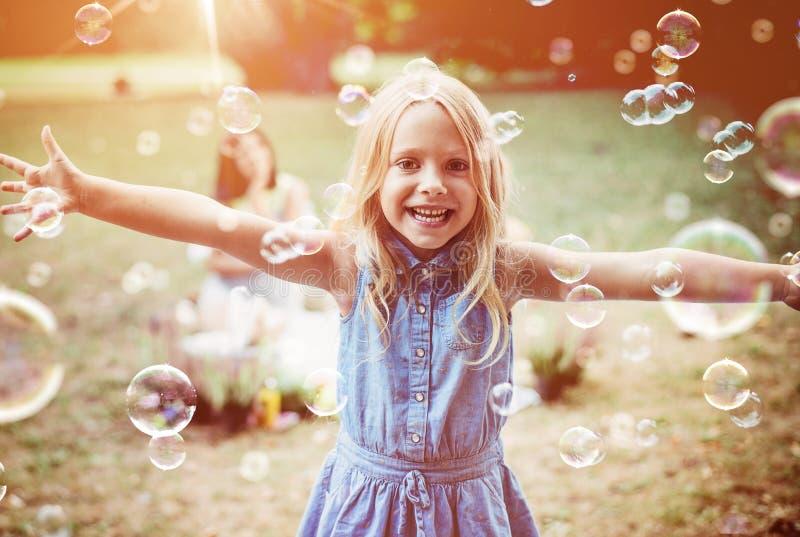 Menina alegre que aprecia o sopro da bolha imagens de stock