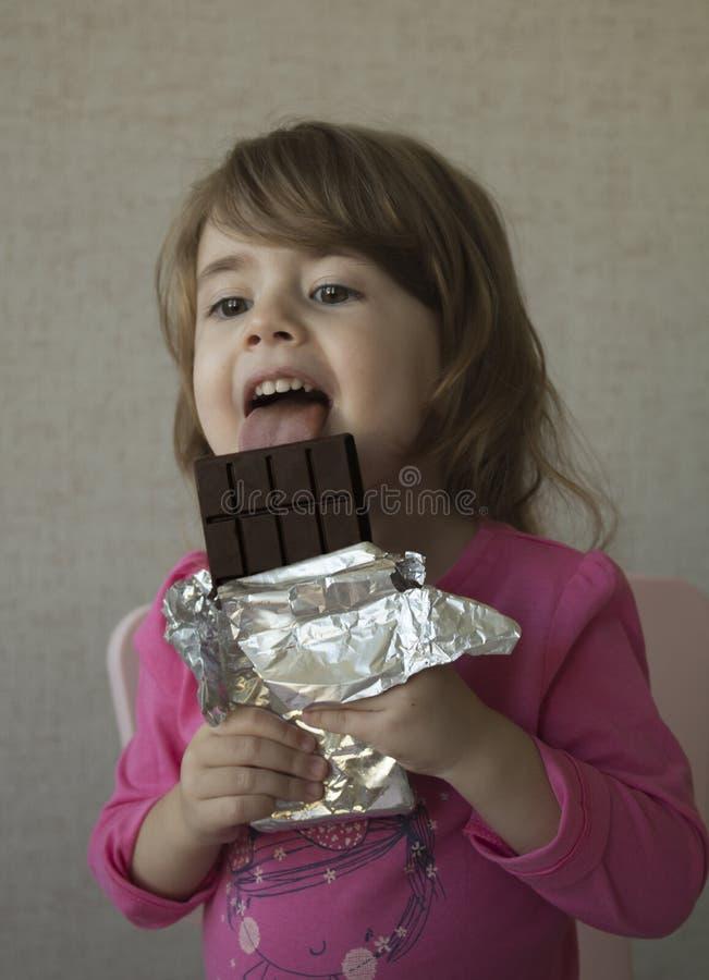 Menina alegre que come o chocolate imagem de stock