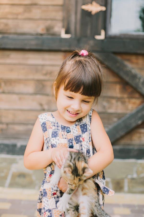 Menina alegre que guarda um gato em seus braços imagem de stock royalty free