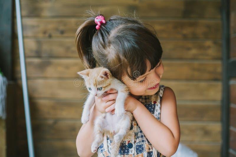 Menina alegre que guarda um gato em seus braços imagens de stock