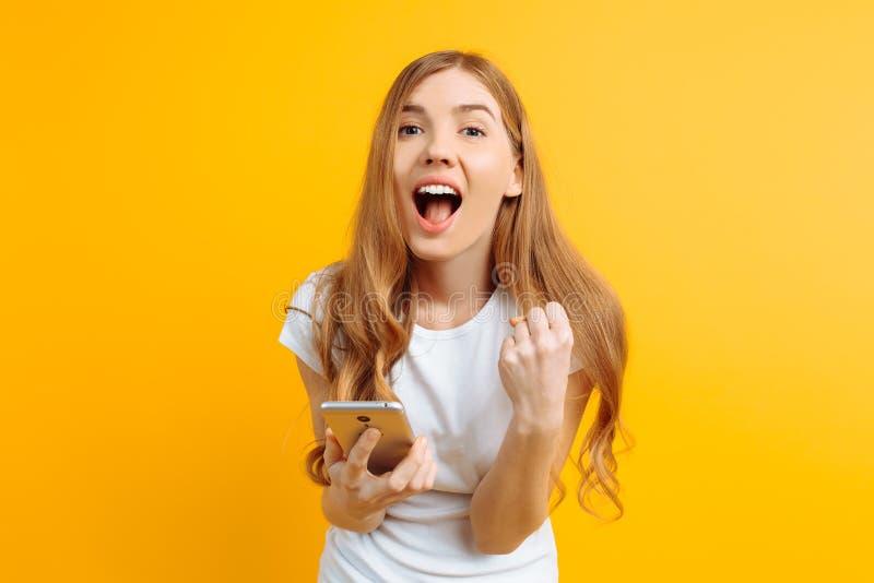 A menina alegre que guarda um telefone celular, comemora a vitória e o sucesso em um fundo amarelo imagens de stock