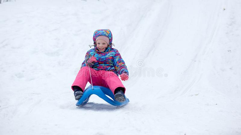 Menina alegre que monta um trenó para baixo em uma fuga coberto de neve do pequeno trenó em uma paisagem ensolarada branca da mon imagem de stock