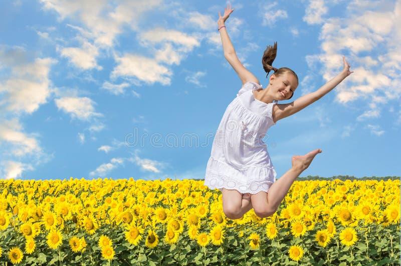 Menina alegre que salta em um fundo dos girassóis fotografia de stock