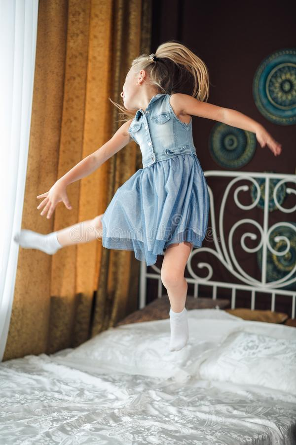 Menina alegre que salta na cama Os risos e os saltos da menina Em uma cama branca, a menina está tendo o divertimento e o salto P foto de stock