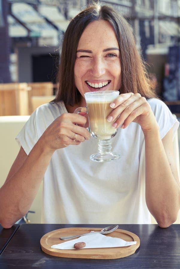 Menina alegre que senta-se em um café fotos de stock royalty free