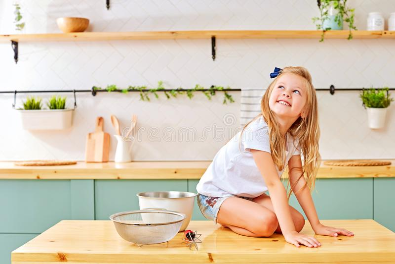 Menina alegre que senta-se na mesa de cozinha imagem de stock