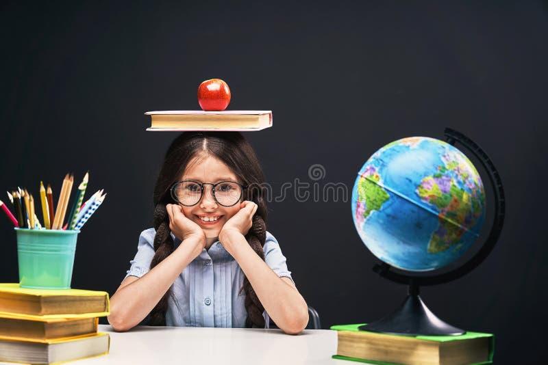 Menina alegre que senta-se na tabela com lápis e livros de texto dos livros Aluno feliz da criança que faz trabalhos de casa na t imagem de stock